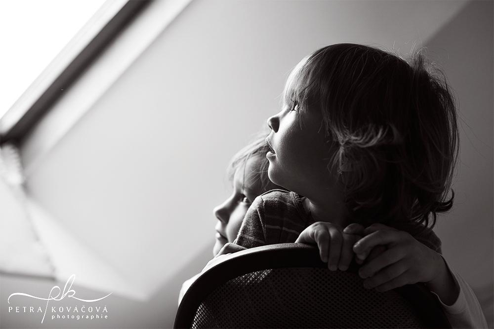 photo noir et blanc de deux filles regardant par la fenêtre